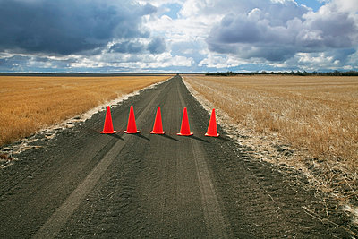 Safety cones lined up across a rural road;Saskatchewan canada - p442m837585f by Benjamin Rondel