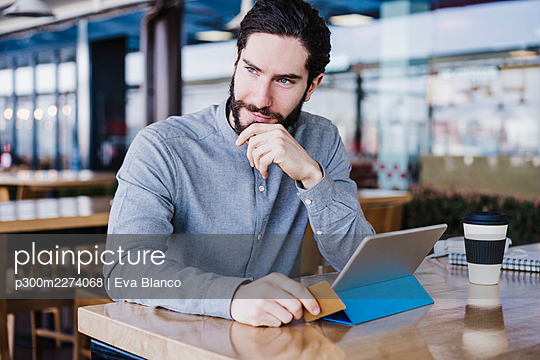 Contemplative businessman with digital tablet and credit card at desk in office - p300m2274068 by Eva Blanco
