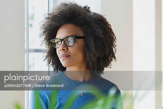 Woman contemplating while looking through window at home - p300m2277498 by Steve Brookland