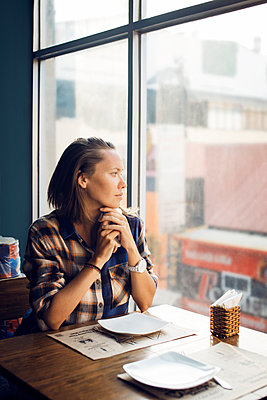 Thoughtful woman looking through window while sitting in cafe - p1166m1145281 by Cavan Images