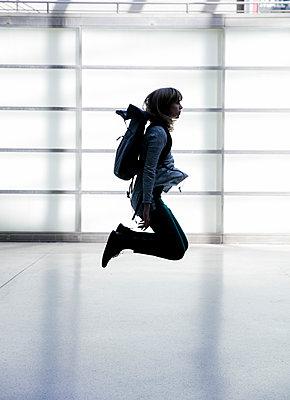 Junge Frau springt im Bahnhof - p1212m1137068 von harry + lidy