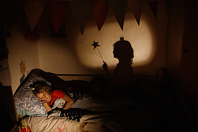Girl sleeps in bed, silhouette of fairy on the wall - p1642m2222197 by V-fokuse