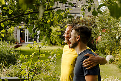 Son and father looking away while standing in back yard - p300m2276949 by Gustafsson