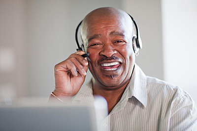 Businessman talking on headset - p429m746808f by Zero Creatives