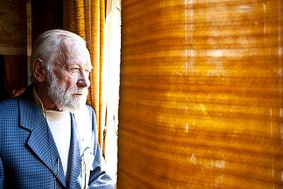 Elderly man looking out of a window - p713m777168 by Florian Kresse