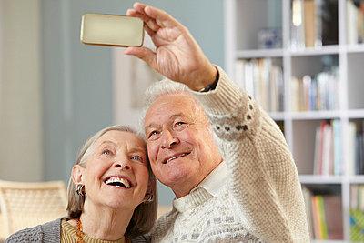 Senior couple using camera phone - p924m699307f by Nick White