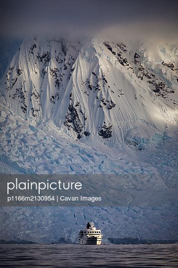 Ship in front of snowy peaks - p1166m2130954 by Cavan Images