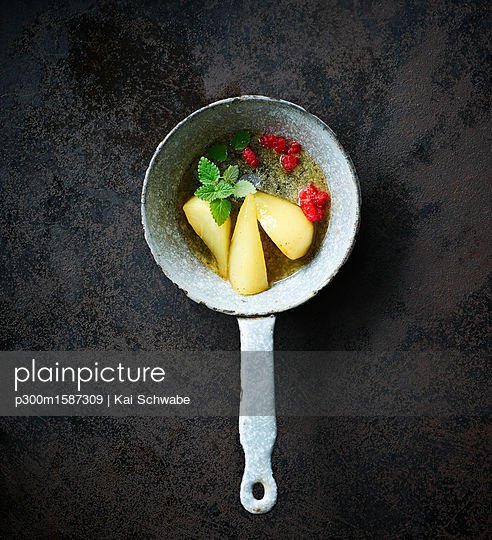 Tonka bean pears and raspberries with mint in a saucepan - p300m1587309 von Kai Schwabe