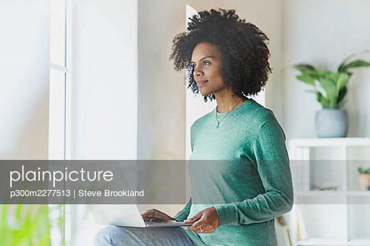 Young thoughtful woman with laptop on lap by window at home - p300m2277513 by Steve Brookland