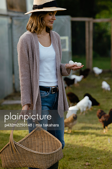 Junge Frau mit Eiern in der Hand - p432m2293148 von mia takahara