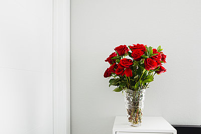 Close-up of roses in vase on table by wall at home - p1166m1524587 by Cavan Images