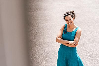 Smiling woman standing backyard with arms crossed - p300m2012757 von Kniel Synnatzschke
