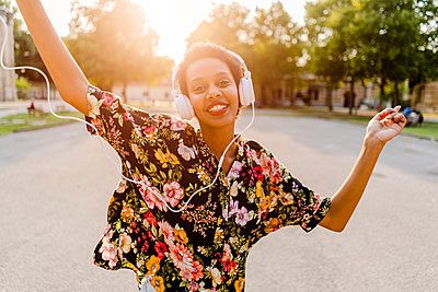 Happy fashionable young woman with headphones dancing outdoors at sunset - p300m2041978 von Giorgio Fochesato