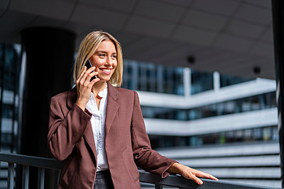 Smiling young businesswoman on the phone in the city - p300m2143647 by Daniel Ingold