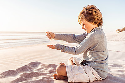 Little boy sitting on windy beach, watching sand trickling from his hands - p300m2167050 by Floco Images