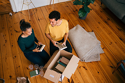 Smiling couple removing novels from box in living room at new home - p426m2138267 by Maskot