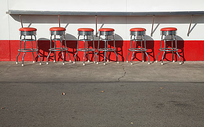 Row of red stools - p495m903935 by Jeanene Scott