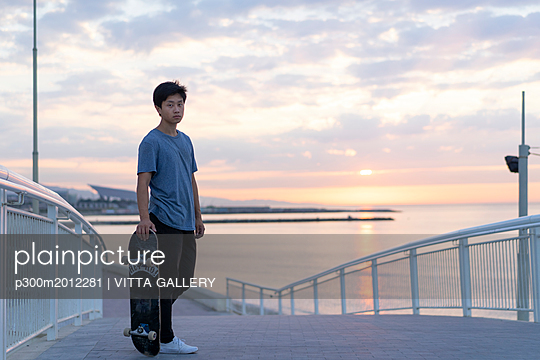 Young Chinese man with skateboard at the beach at sunrise - p300m2012281 von VITTA GALLERY