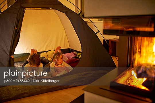 Brother and sister camping in the living room near fire place - p300m2188442 by Dirk Kittelberger