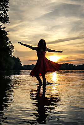 Woman dancing in river - p1019m2098799 by Stephen Carroll