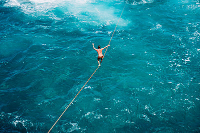 High angle view of carefree young man practicing slacklining over sea - p1166m2066941 by Cavan Images