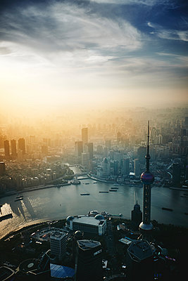 Aerial view of modern cityscape by Huangpu River against cloudy sky during sunset - p1166m2105865 by Cavan Images