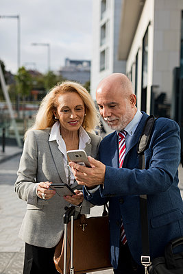 Senior businessman and businesswoman with baggage using cell phones in the city - p300m2070352 von Mauro Grigollo
