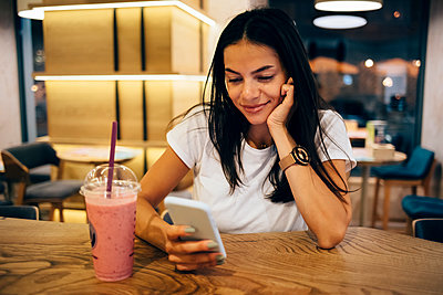 Black-haired woman drinking a smoothie and using smartphone in cafe - p300m2160279 by alev