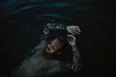 Man with eyes closed floating on water in sea - p300m2274839 by Gala Martínez López