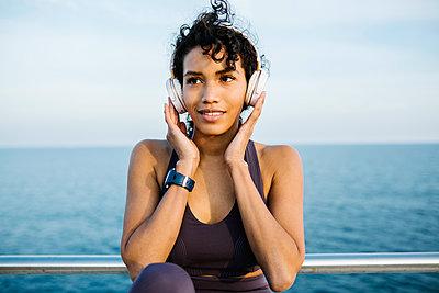 Sportswoman listening music through headphones in front of sea - p300m2277731 by Xavier Lorenzo