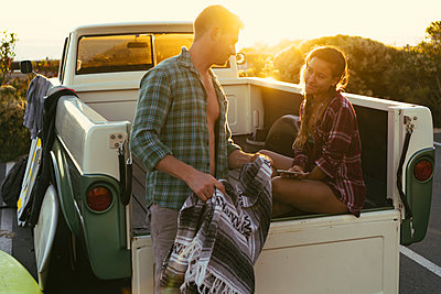 Surfing couple in back of pickup truck at sunset at Newport Beach, California, USA - p924m1224755 by Kevin Kozicki