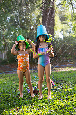 Girls with buckets on head playing with garden sprinkler - p924m1468706 by Kinzie Riehm