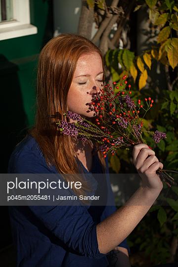 An einem Beeren-Strauch riechend - p045m2055481 von Jasmin Sander