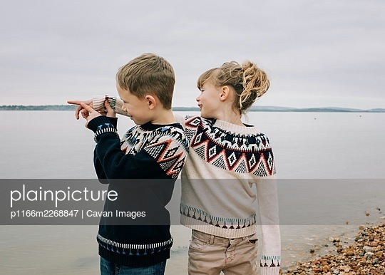 brother and sister playing at the beach together pointing to the sea - p1166m2268847 by Cavan Images