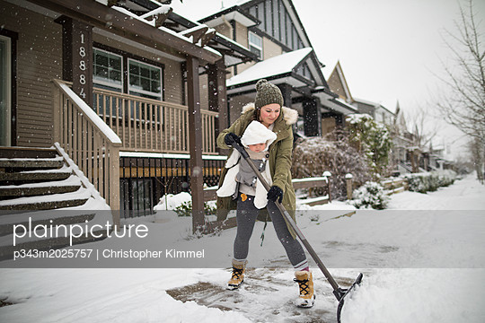 Mother with son shoveling snow in winter - p343m2025757 by Christopher Kimmel