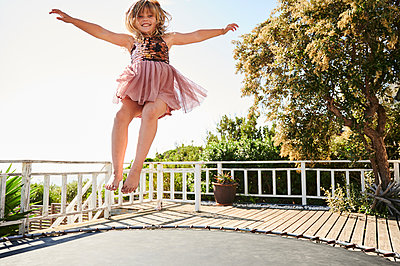 Little girl jumping on trampoline - p1640m2244886 by Holly & John