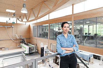 Confident businesswoman with arms crossed leaning on railing in factory - p300m2265169 by Florian Küttler