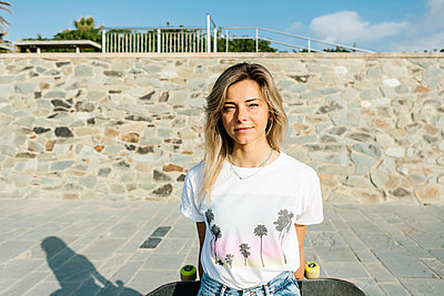 Blond woman with skateboard at wall - p300m2282982 by Xavier Lorenzo