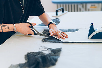 Fashion designer cutting fabric from dressmaker's pattern - p429m2058358 by Eugenio Marongiu