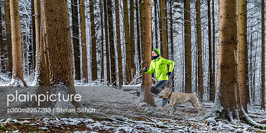 Young male sportsperson running with labrador during winter in forest - p300m2257283 by Stefan Schurr