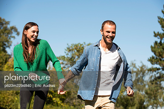 Smiling young couple walking in public park - p623m2294840 by Eric Audras