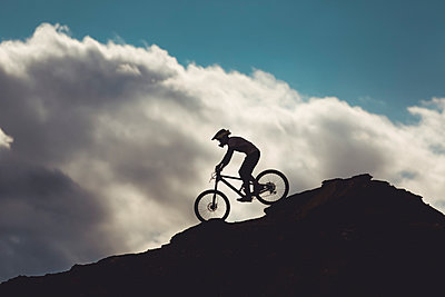 side view of young male on mountain bike riding over rocks in Utah - p1166m2162914 by Cavan Images