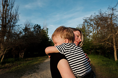Mother and son hugging in park - p1363m2134659 by Valery Skurydin