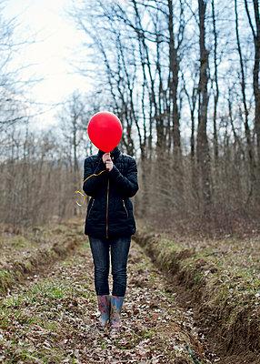 Girl hiding face behind a red balloon - p1412m1548048 by Svetlana Shemeleva