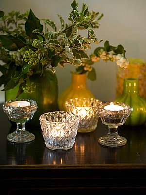 Cut glass tealights with holly in ceramic vases - p349m2167787 by Polly Wreford