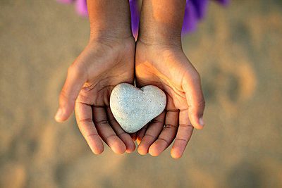 Young hands holding heart shaped rock - p3723089 by James Godman
