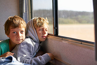 Boys sitting in campervan looking out of window, Polonio, Rocha, Uruguay, South America - p429m1519601 by Stephen Lux