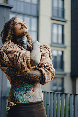 Handsome tattooed sexy man with long hair and mustache outdoors - p1166m2147644 by Cavan Images