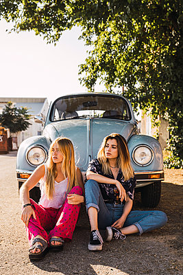 Two young women sitting outside at a vintage car - p300m2023588 von Kike Arnaiz