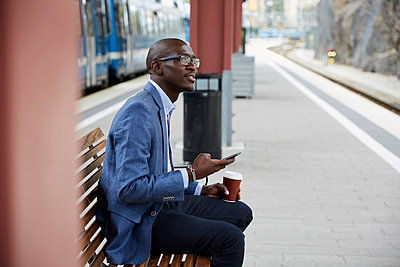 Thoughtful businessman sitting with smart phone and coffee at railroad station - p426m2072537 by Maskot